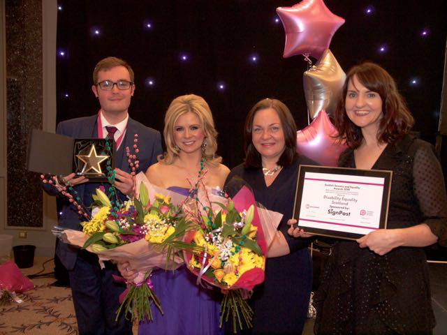 Ian Buchanan, Morven Brooks and Emma Scott from Disability Equality Scotland collect their award, presented by Kelly-Ann Woodland from STV News.